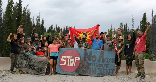 A group picture of Unist'ot'en allies, holding a warrior flag, fists raised, a sign saying no access without consent. Are these people passive, disruptive, or volatile according to RCMP check lists?